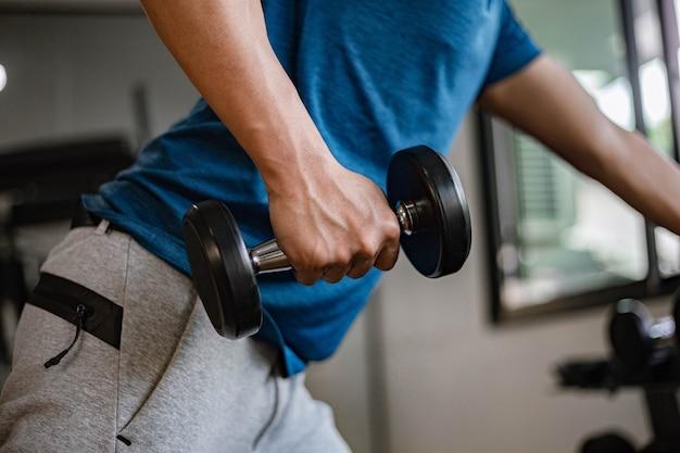 Concept de gym d'entraînement un jeune adulte utilisant son bras musclé et puissant soulevant un haltère vers le haut et vers le bas dans la salle de gym.