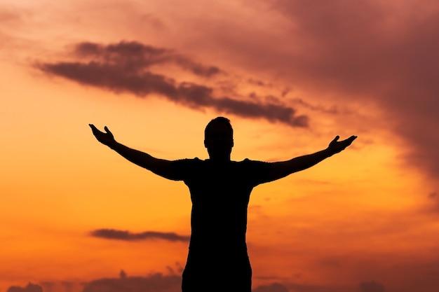 Concept habilité avec silhouette d'homme fort avec les mains levées au coucher du soleil
