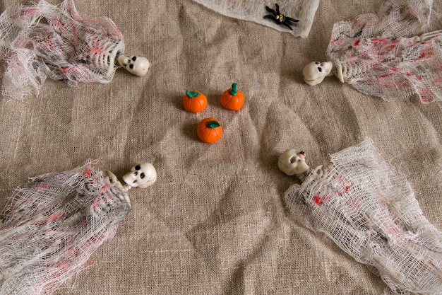 Concept d'halloween avec des araignées citrouilles, squelettes et jouets sur fond gris froissé.