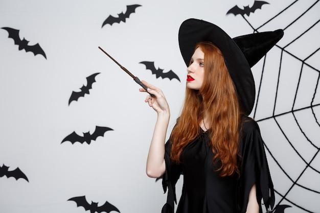 Concept d'halloween - belle sorcière jouant avec un bâton magique sur un mur gris.