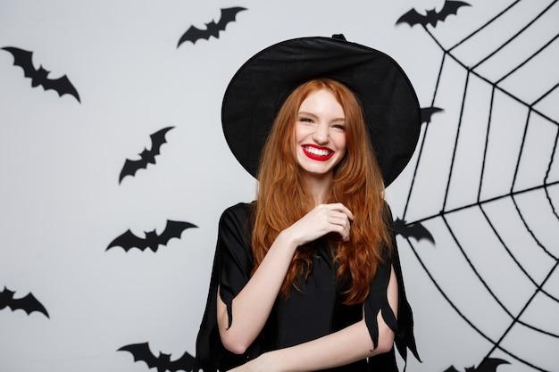Concept d'halloween - belle sorcière tenant la main et souriant sur un mur gris.