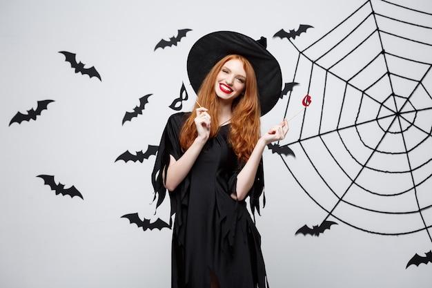 Concept d'halloween - belles filles en robes de sorcière noires tenant des accessoires de fête.