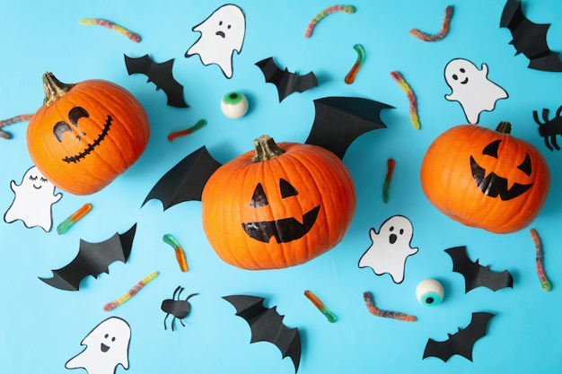 Concept d'halloween avec des citrouilles, des fantômes, des bonbons et des chauves-souris