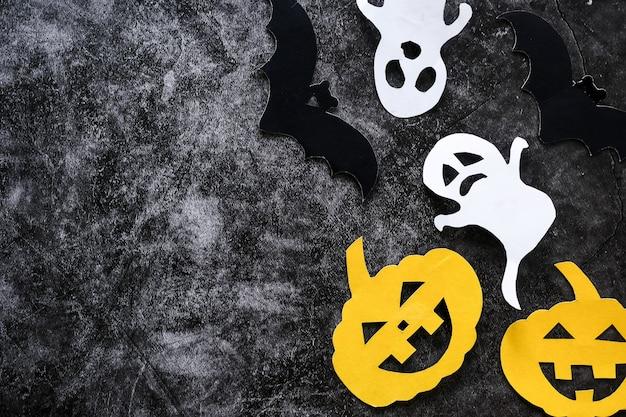 Concept d'halloween avec des citrouilles, des fantômes et des chauves-souris couper du papier sur fond de béton noir.