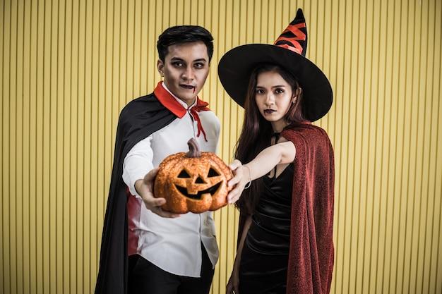 Concept d'halloween de jeune femme asiatique en costume de sorcière et homme asiatique en costume dracula sur fond jaune. portrait teen couple déguisé en sorcières et dracula pour célébrer le festival d'halloween.