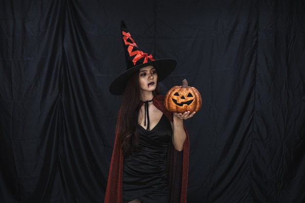 Concept d'halloween de jeune femme asiatique en costume de sorcière et tenir halloween citrouille orange sur fond de tissu noir. portrait d'une femme adolescente déguisée en sorcière pour célébrer le festival d'halloween.