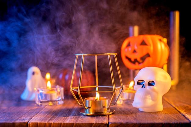 Concept d'halloween, lanterne de citrouille orange et bougies sur une table en bois sombre avec de la fumée bleu-orange autour de l'arrière-plan, trick or treat, gros plan