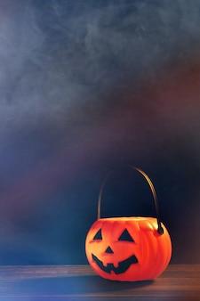 Concept d'halloween - lanterne citrouille en plastique orange sur une table en bois sombre avec une lumière scintillante floue en arrière-plan, trick or treat, close up