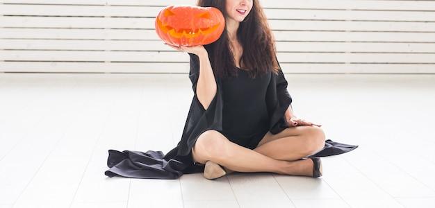 Concept d'halloween et de mascarade - belle jeune femme close-up posant avec citrouille jack-o'-lantern
