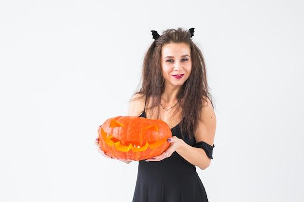 Concept d'halloween et de mascarade - belle jeune femme posant avec citrouille jack-o'-lantern
