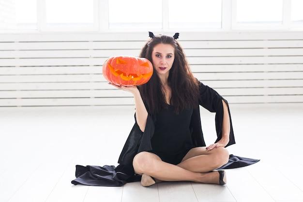 Concept d'halloween et de mascarade - belle jeune femme posant avec citrouille jack-o'-lantern.