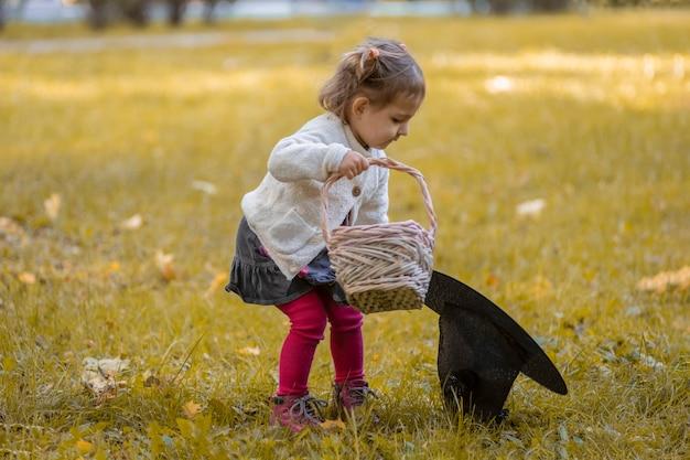 Concept d'halloween. mignonne petite fille jouant avec un chapeau de sorcière dans le parc en automne.