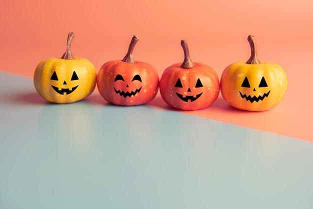 Concept d'halloween, quatre citrouilles avec sourire visage sur fond de couleurs pastel.