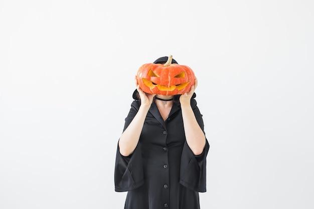 Concept d'halloween - sorcière anonyme avec citrouille jack-o'-lantern sur surface lumineuse