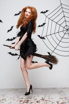 Concept d'halloween, une sorcière élégante et heureuse aime jouer avec un balai fête d'halloween sur un mur gris