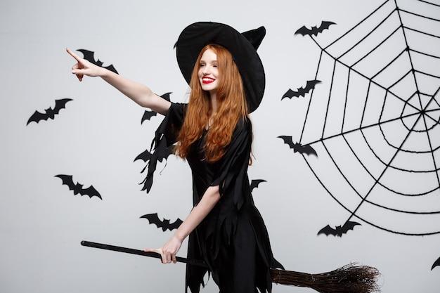 Concept d'halloween, une sorcière élégante et heureuse aime jouer avec un manche à balai