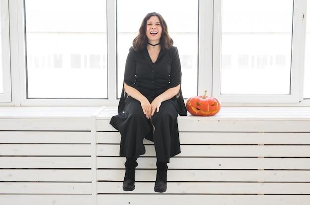 Concept d'halloween - sorcière heureuse avec citrouille jack-o'-lantern sur mur lumineux.