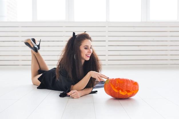 Concept d'halloween - sorcière heureuse avec citrouille jack-o'-lantern