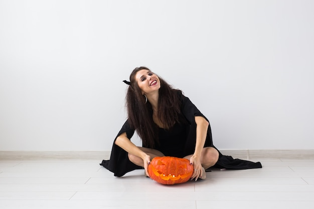 Concept d'halloween - sorcière heureuse avec citrouille jack-o'-lantern.