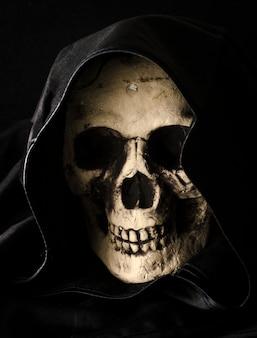 Concept d'halloween de tête de crâne effrayant dans le capot noir