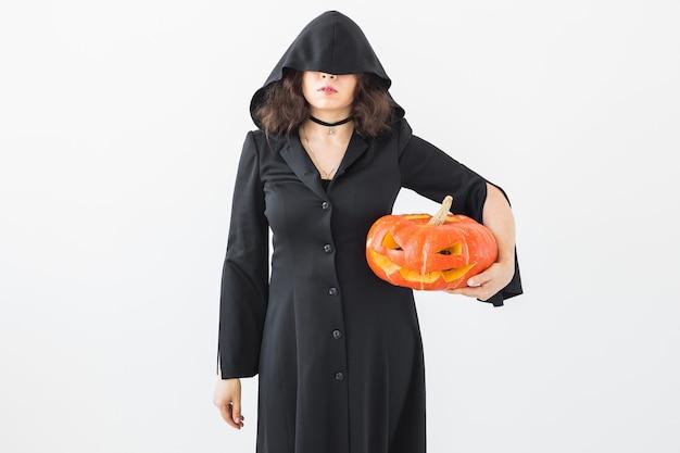 Concept d'halloween et de vacances - femme sorcière avec citrouille jack o'lantern