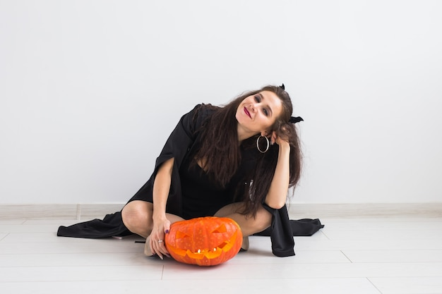 Concept d'halloween et de vacances - femme sorcière avec citrouille jack o'lantern.