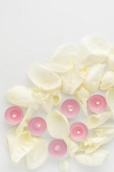 Concept d'harmonie. brûler des bougies d'arôme et des pétales de fleurs sur blanc. mise à plat, espace copie. verticale