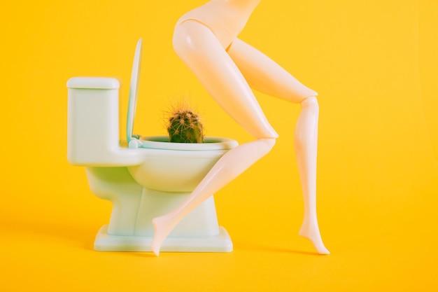 Concept d'hémorroïdes, la poupée est assise sur des toilettes miniatures avec un cactus à l'intérieur de l'espace de copie de fond jaune