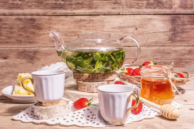 Concept de l'heure du thé. thé à la menthe aromatique, fraises mûres, miel doux. une boisson chaude, des tasses en céramique sur socle, une serviette en lin vintage. vieux fond de planches de bois, espace de copie