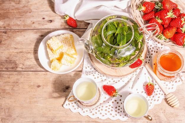 Concept de l'heure du thé. thé à la menthe aromatique, fraises mûres, miel doux. une boisson chaude, des tasses en céramique sur socle, une serviette en lin vintage. vieux fond de planches de bois, vue de dessus