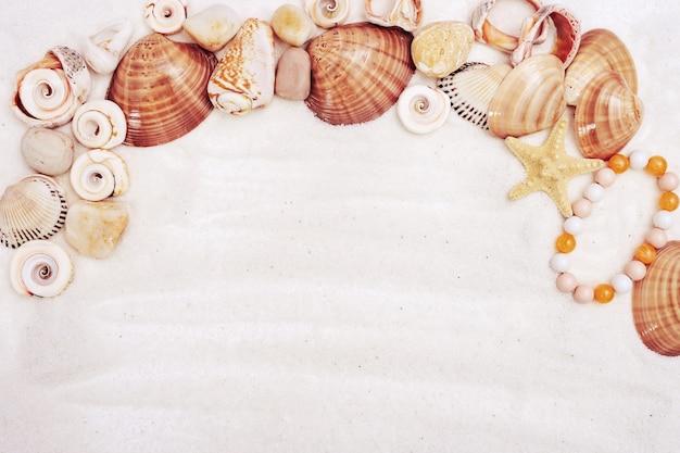Concept de l'heure d'été avec des coquillages, étoiles, cailloux de mer, bracelet femme sur sable blanc avec espace de copie.