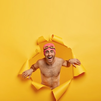 Concept de l'heure d'été. un homme souriant ravi se détend en mer et dispose d'une station thermale, se tient nu dans un trou de papier