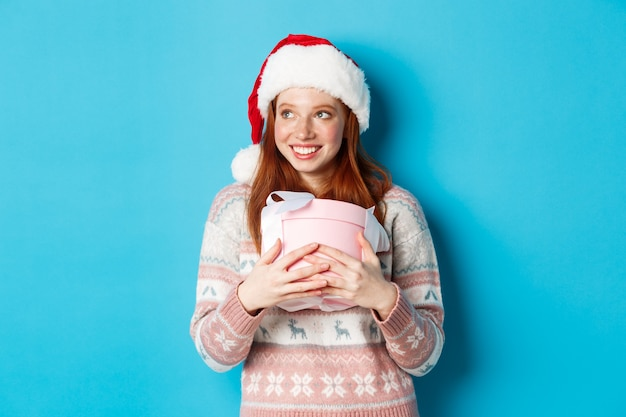 Concept d'hiver et de célébration. rousse rêveuse en bonnet de noel serrant son cadeau de noël et regardant à gauche, souriante heureuse, debout sur fond bleu.