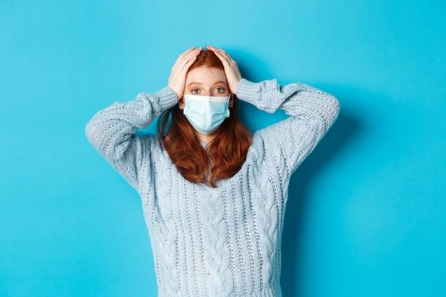 Concept d'hiver, de covid-19 et de distanciation sociale. fille rousse troublée dans un masque facial regardant en détresse, tenant les mains sur la tête en panique, debout sur fond bleu