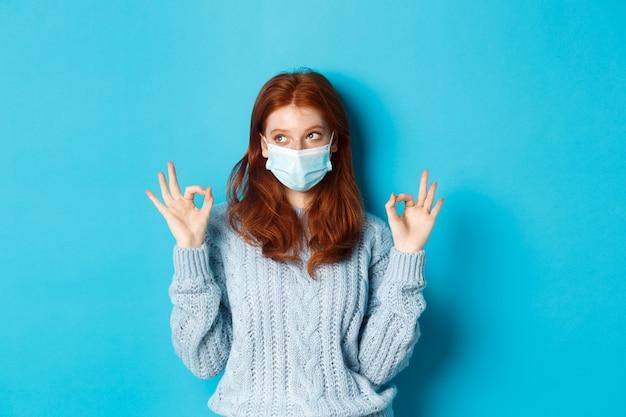 Concept d'hiver, de covid-19 et de distanciation sociale. jeune femme rousse satisfaite en masque facial montrant des gestes corrects et corrects et regardant à gauche la promo, fond bleu.
