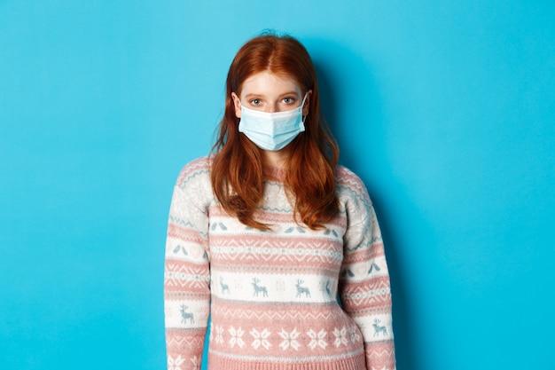 Concept d'hiver, de covid-19 et de quarantaine. jeune fille rousse en pull et masque facial regardant la caméra, debout sur fond bleu.
