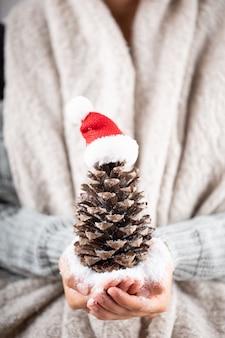 Concept d'hiver jeunes mains tenant un décor de noël. idée de décoration de noël. décor de noël dans les mains d'une femme, fond avec bokeh doré.