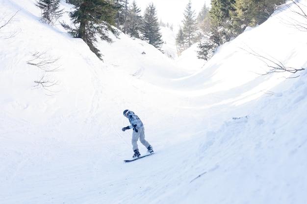 Concept d'hiver, de loisirs, de sport et de personnes - snowboarder actif sautant dans les montagnes par une journée ensoleillée. planche à neige agrandi. station de ski de sheregesh