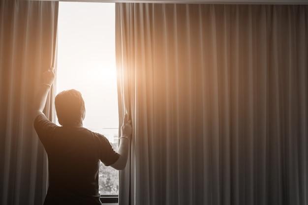 Concept homme et espoir. homme ouvrant des rideaux de fenêtre