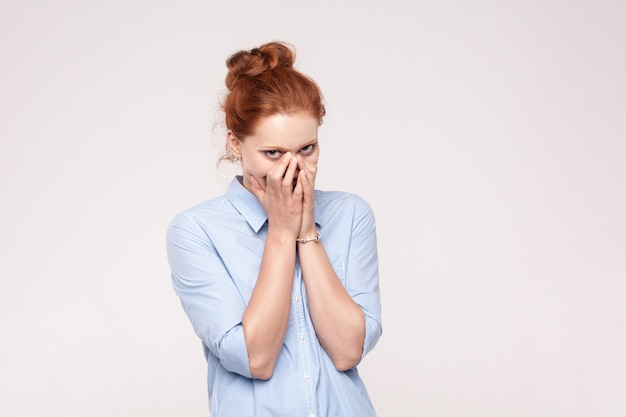 Concept de honte et de menteur. femme aux cheveux rouges couvrant la bouche avec les deux mains gardant un secret et peu souriant. belle femme rousse en chemise bleue. studio isolé tourné sur fond gris.