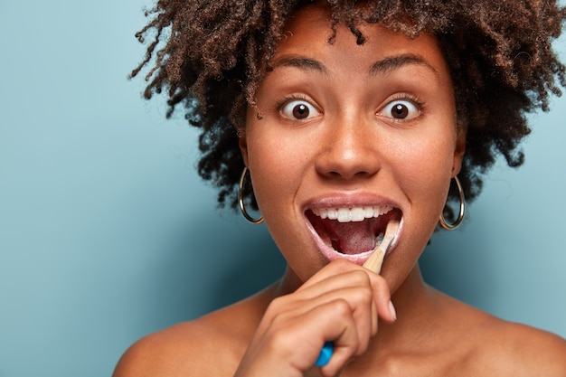 Concept d'hygiène dentaire et de dentisterie. tête de jeune femme afro-américaine surprise avec des cheveux croquants, utilise une brosse à dents et du dentifrice pour nettoyer les dents, regarde avec des yeux bugged isolé sur bleu