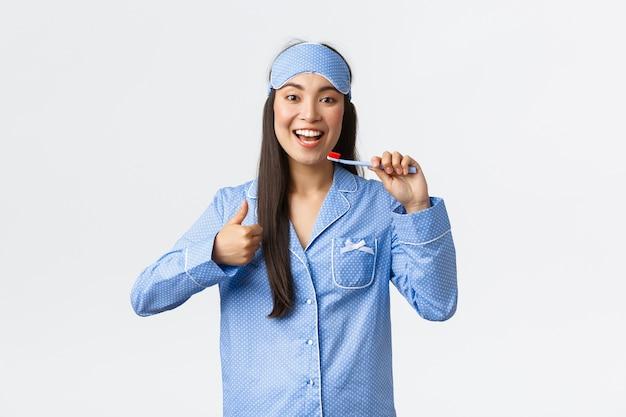 Concept d'hygiène, de style de vie et de personnes à la maison. heureux fille asiatique heureuse en jammies et masque de sommeil, montrant les pouces vers le haut tout en se brossant les dents blanches avec une brosse à dents, recommande le dentifrice.
