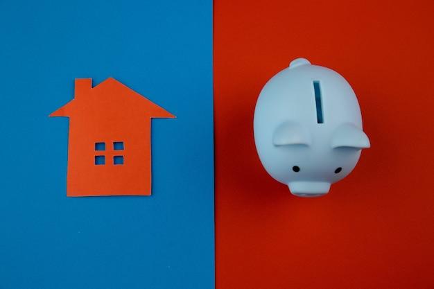 Concept d'hypothèque. petite maison en papier à côté d'une tirelire sur coloré.