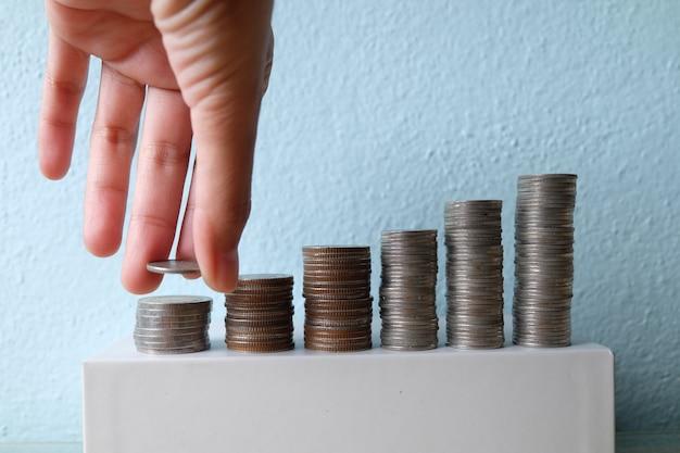 Concept d'idée d'entreprise, main mettre l'empilement de pièces sur l'argent