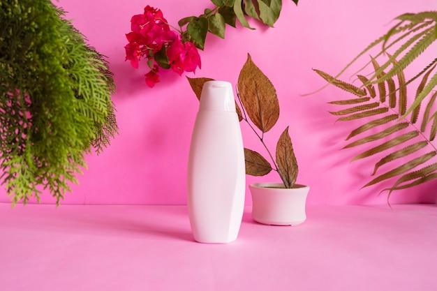 Concept d'idées de composition mettant en vedette des produits. bouteilles cosmétiques sur fond rose décorées de feuilles séchées, de feuilles de pin et de fleurs rouges
