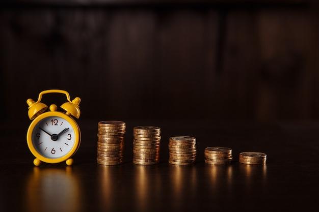 Concept d'idées financières d'entreprise avec pile de pièces et réveil sur fond de bois.