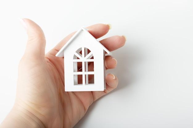 Concept d'immobilier achetant une maison. la main femelle tient la maison de jouet blanche en bois