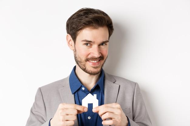 Concept immobilier et assurance. agent immobilier masculin souriant montrant petite découpe de maison de papier et regardant la caméra, vente de propriété, fond blanc.