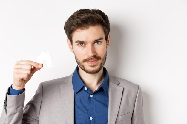 Concept immobilier et assurance. bouchent le portrait de bel homme barbu en costume montrant la petite découpe de maison de papier et regardent fond blanc, assertif.