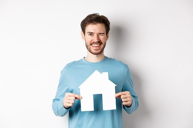 Concept immobilier et assurance. heureux jeune homme clignant des yeux et souriant, montrant la découpe de maison de papier, debout sur fond blanc.